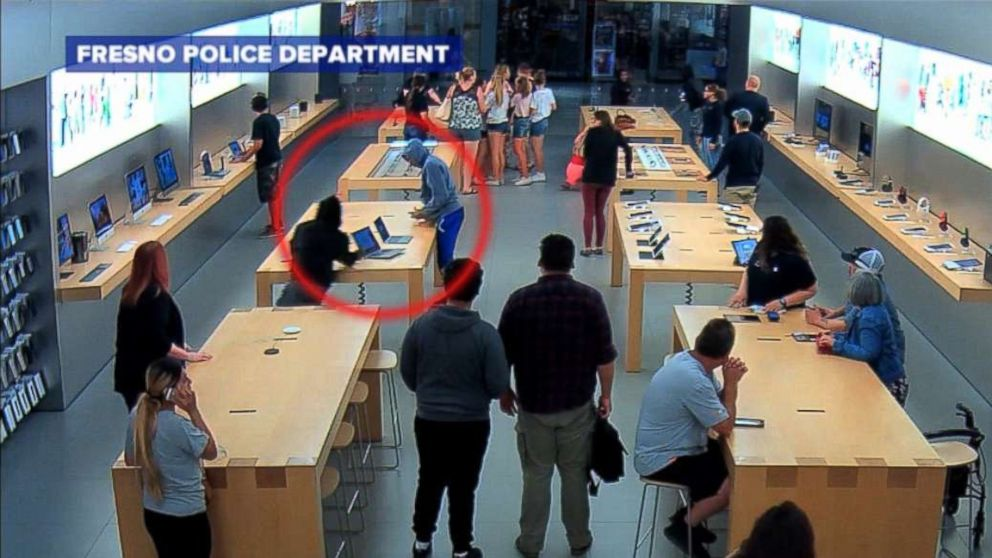 The two people seen in this inset allegedly ran into this Apple store stealing merchandise worth thousands of dollars.