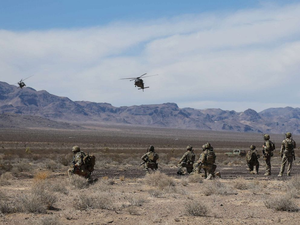PHOTO: U.S. Special Forces Soldiers and Airmen from the 99th Civil Engineer Squadron EOD team and 66th Rescue Squadron, watch as two UH-60 Blackhawk helicopters land at the Nevada Test and Training Range near Nellis AFB, Nevada, Aug. 28, 2018.