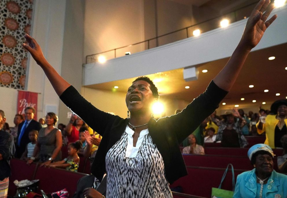 PHOTO: Avis Doughton holds her arms up as the Rev. Jesse Jackson speaks celebrating the life of singer Aretha Franklin at her fathers church, New Bethel Baptist, during a Sunday morning service in Detroit, August 19, 2018.