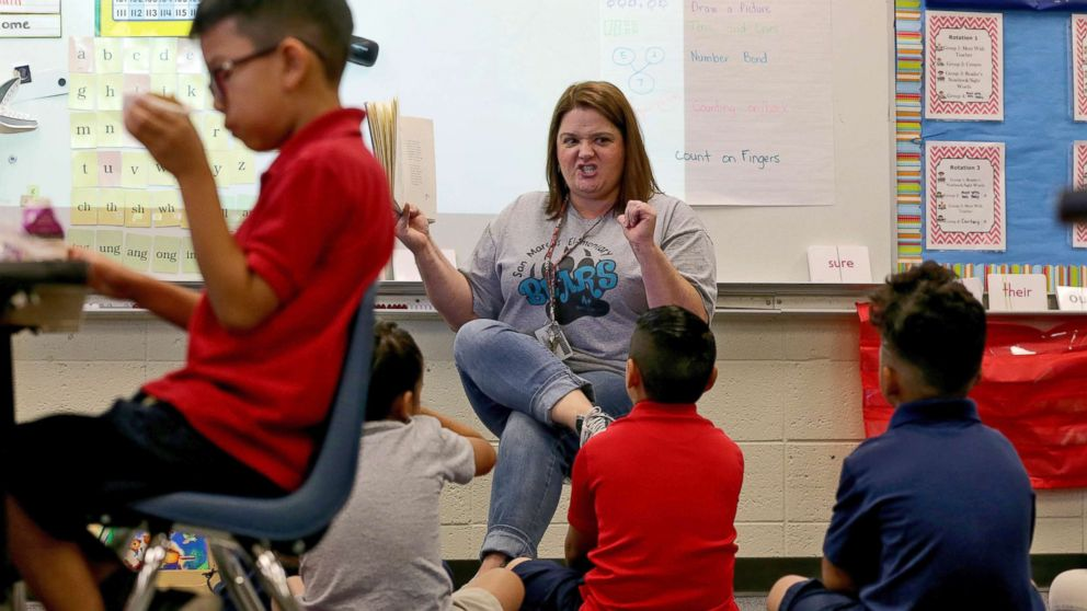 Third grade teacher Jennifer Boettcher reads a story to kids as they eat breakfast at San Marcos Elementary School, May 4, 2018, in Chandler, Ariz., after a statewide teachers strike ended.