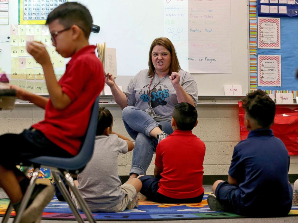 PHOTO: Third grade teacher Jennifer Boettcher reads a story to kids as they eat breakfast at San Marcos Elementary School, May 4, 2018, in Chandler, Ariz., after a statewide teachers strike ended.