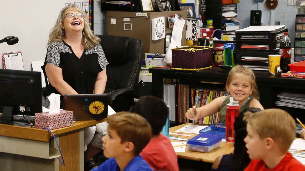 Cindy Cordts, a third grade teacher at Oakwood Elementary School, laughs along with some of her students as schools opened after a statewide teachers strike ended Friday, May 4, 2018, in Peoria, Ariz.