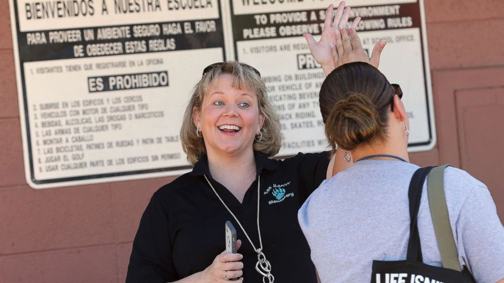 Principal Dr. Becky Henderson high-fives teachers arriving for work at San Marcos Elementary School, May 4, 2018, in Chandler, Ariz.