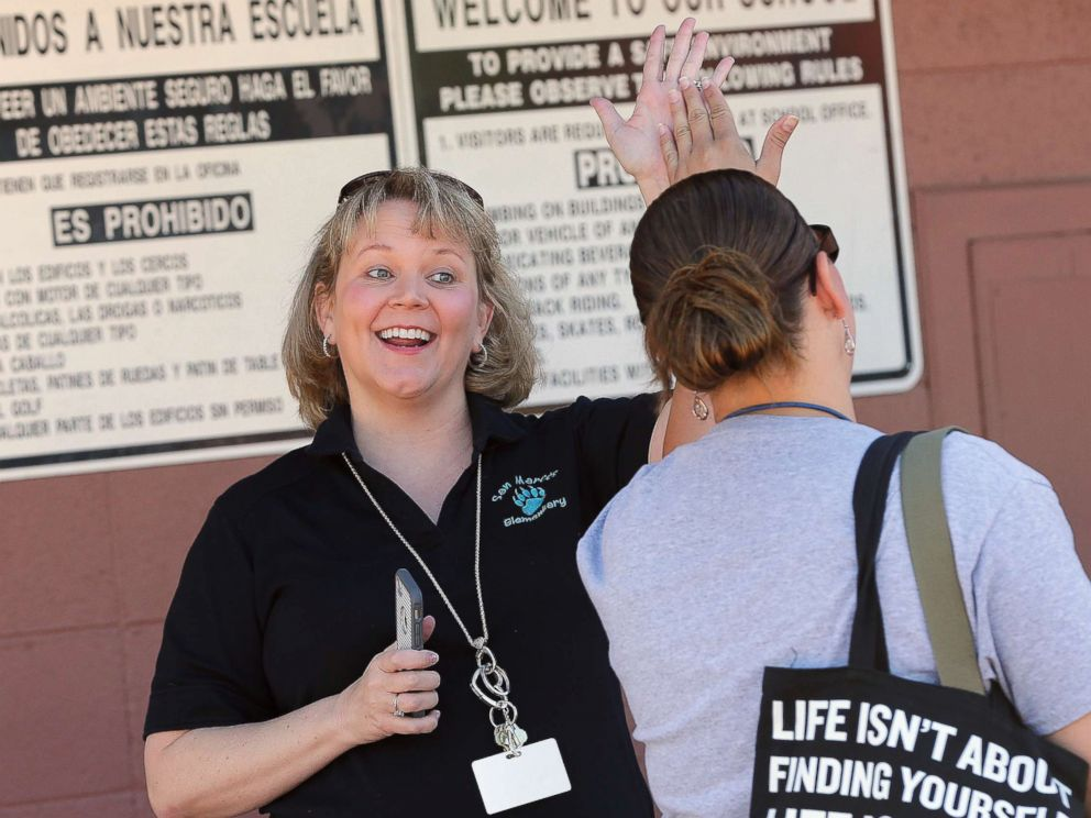 PHOTO: Principal Dr. Becky Henderson high-fives teachers arriving for work at San Marcos Elementary School, May 4, 2018, in Chandler, Ariz.