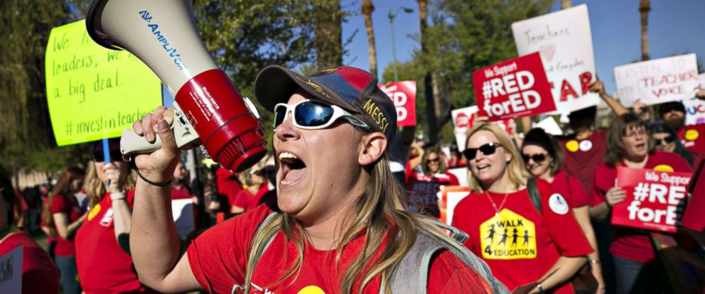 PHOTO: Lindsay Breon, a Physical Education teacher at Washington Elementary School in Phoenix, shouts into a megaphone while rallying to support teachers during a #RedForEd rally at the Arizona State Capitol, in Phoenix, March 28, 2018.