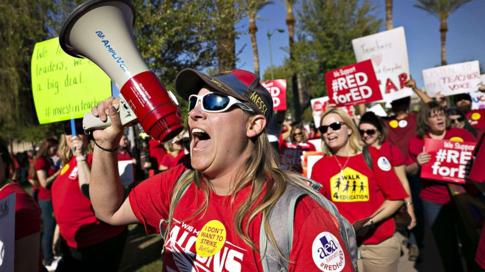 Lindsay Breon, a Physical Education teacher at Washington Elementary School in Phoenix, shouts into a megaphone while  rallying to support teachers during a #RedForEd rally at the Arizona State Capitol, in Phoenix, March 28, 2018.