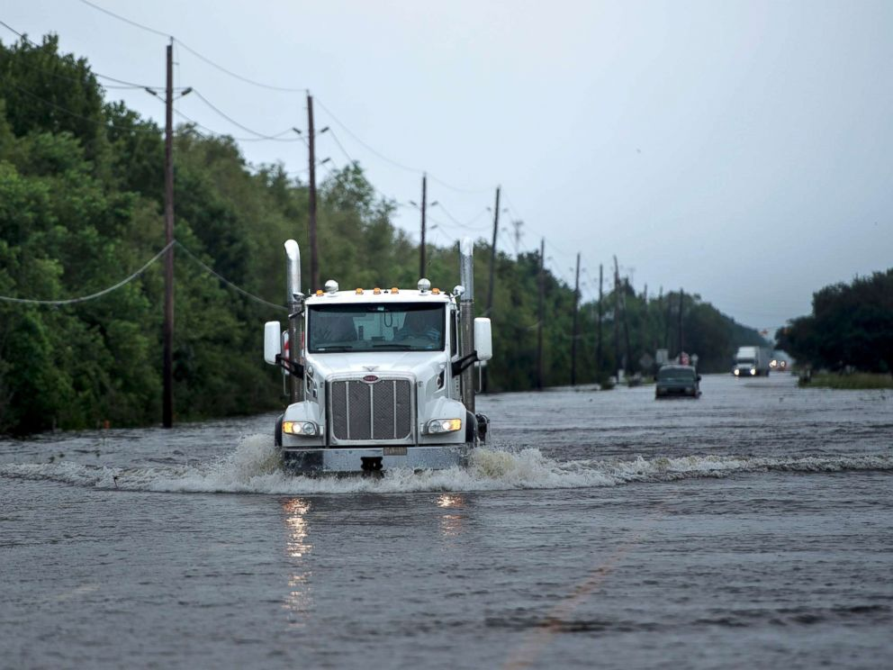 PHOTO: Trucks make their way through flood waters on a main road leading to the Arkema Inc. chemical plant that was in crisis during the aftermath of Hurricane Harvey, Aug. 30, 2017, in Crosby, Texas.