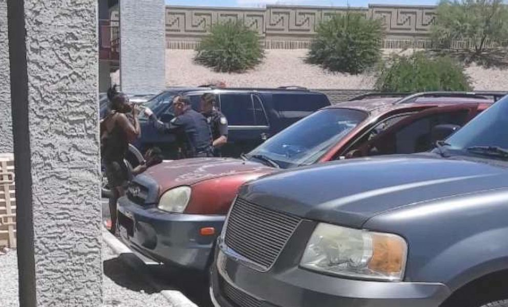 PHOTO: A video on a cell phone shows policemen from the Phoenix Police Department after sweeping Dravon Ames, handcuffed, and pointing a rifle at a pregnant mother with her two young daughters on May 27, 2019.