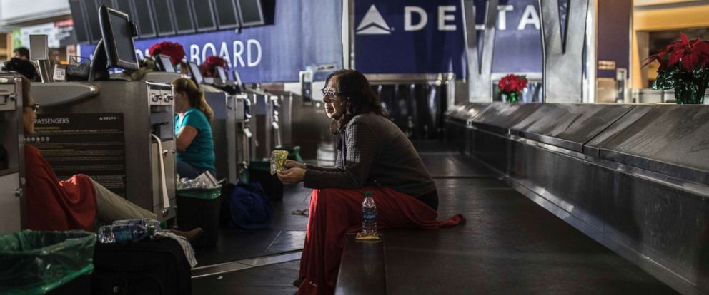 PHOTO: A passenger sits behind the ticket counter after the lights went out at Hartfield-Jackson Atlanta International Airport, Dec. 17, 2017, in Atlanta.