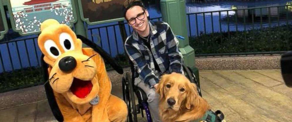 PHOTO: Julian Gavinos Golden Retriever service dog Atlas meets the giant version of Disney character Pluto at Epcot Center in Orlando, Fla., Jan. 19, 2018.