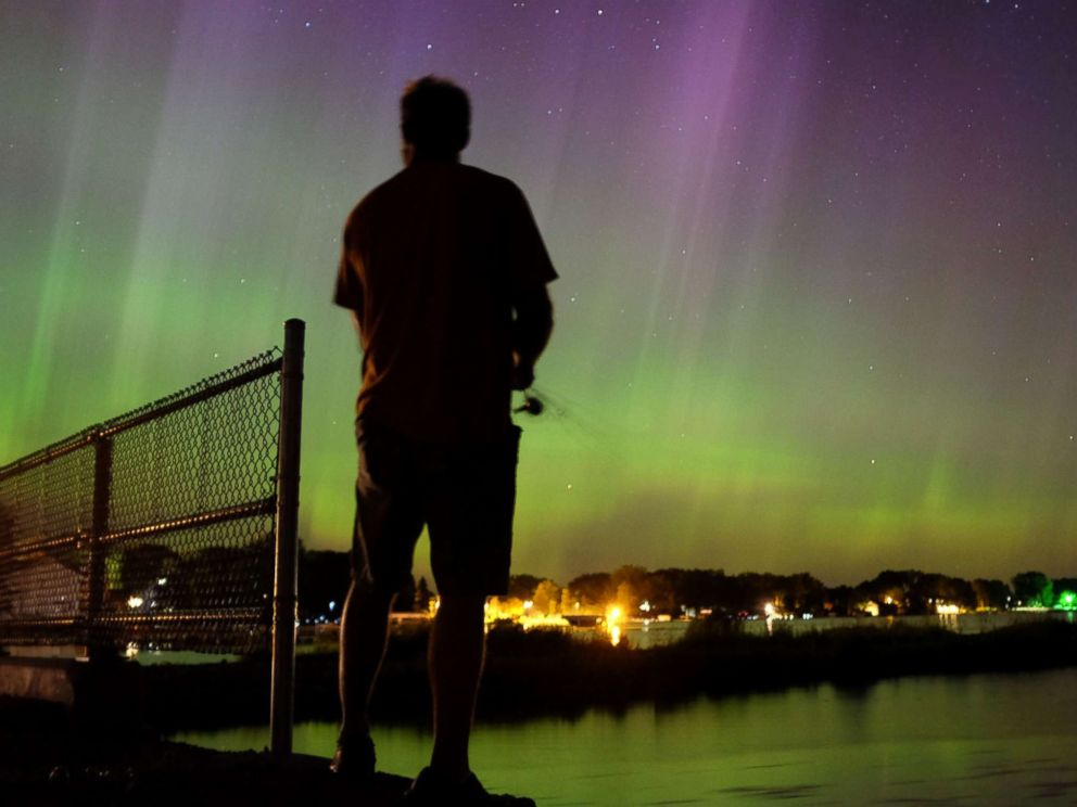 PHOTO: Wade Kitner looks at the northern lights as he fishes in Ventura, Iowa, June 23, 2015.
