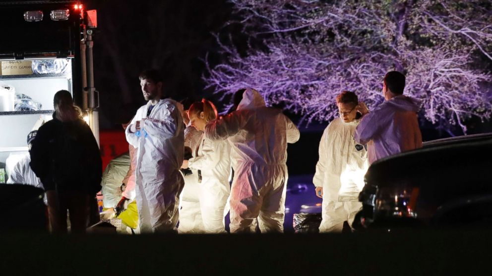 Members of law enforcement work near the area where a suspect in a series of bombing attacks in Austin blew himself up as authorities closed in, March 21, 2018, in Round Rock, Texas.