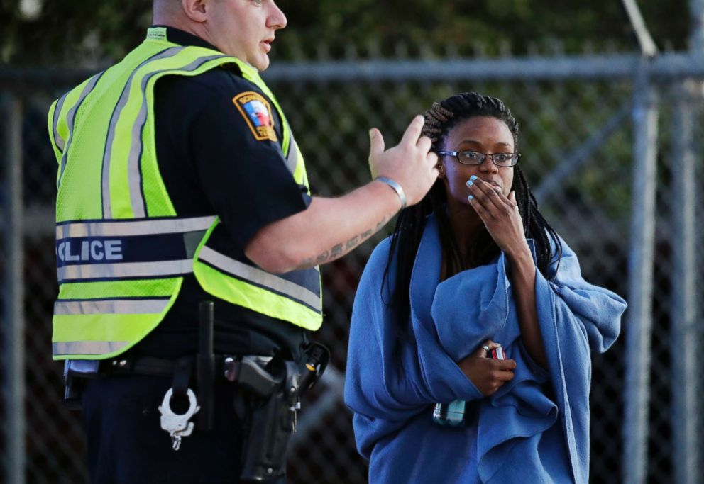 PHOTO: An employee wrapped in a blanket talks to a police officer after she was evacuated at a FedEx distribution center where a package exploded, March 20, 2018, in Schertz, Texas.