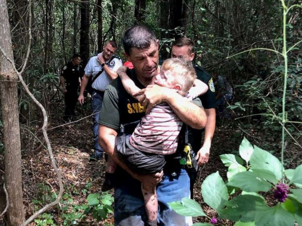 PHOTO: Boy being carried out of forest by his rescuers.