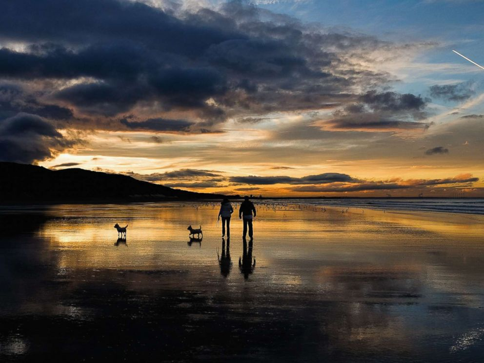 PHOTO: A couple walk their dogs on the beach as the sun sets on the Autumn Equinox, which marks the first day of Autumn, Sept. 23, 2015, in Saltburn, England.