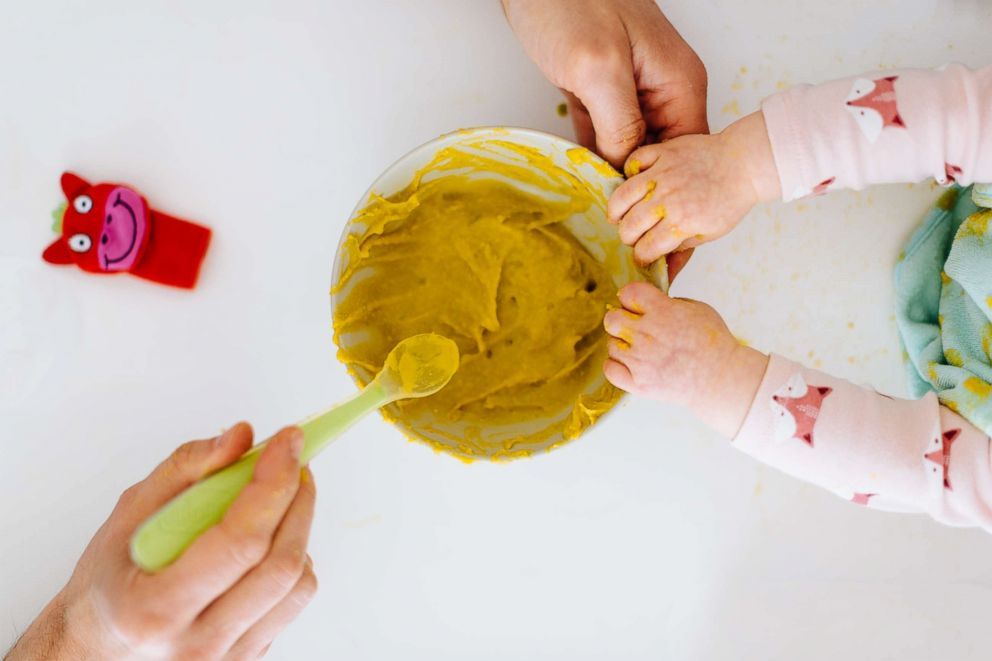 PHOTO: Hand spooning baby food.