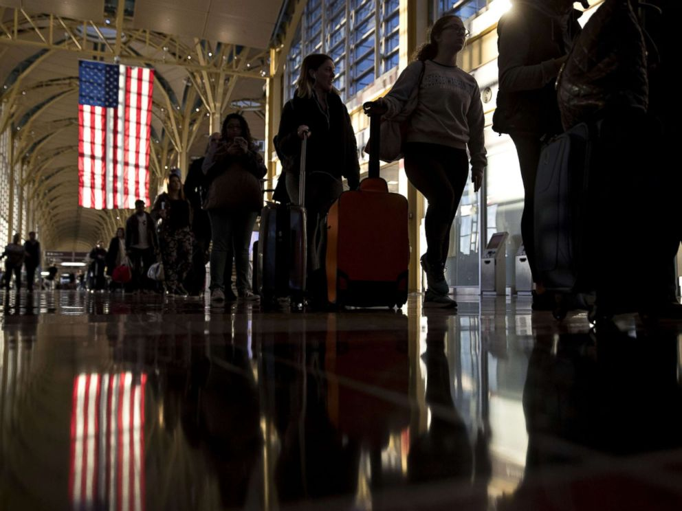 PHOTO: An American flag hangs above travelers waiting in line before going through Transportation Security Administration (TSA) screening at Ronald Reagan National Airport (DCA) in Washington, D.C., Nov. 23, 2016.
