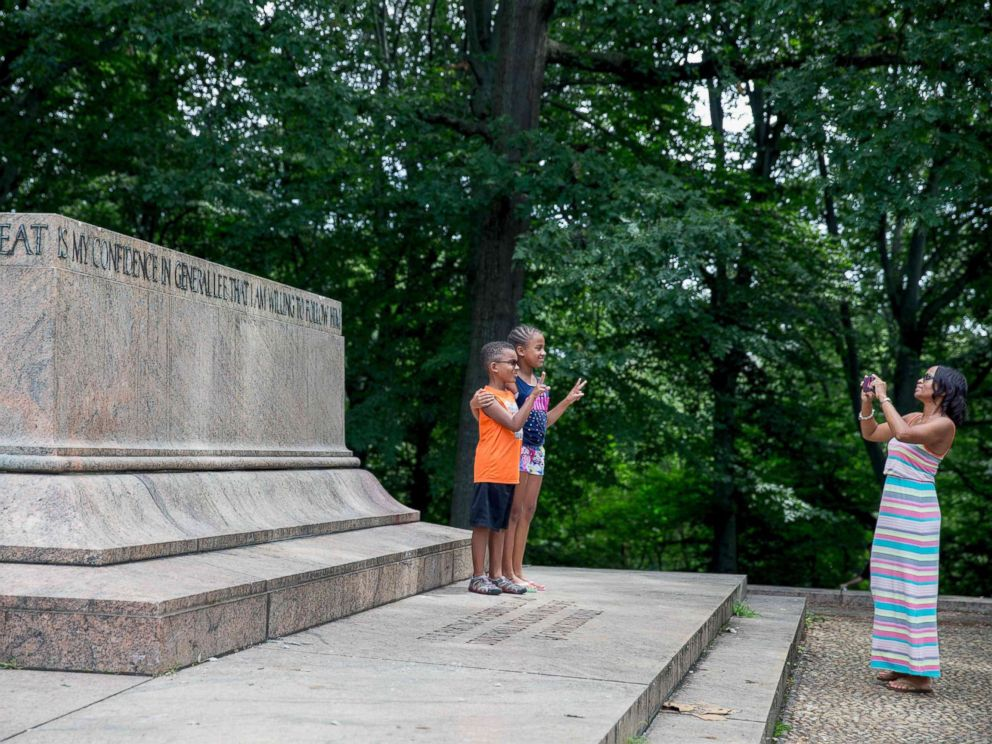 PHOTO: A family takes photos at the Robert E. Lee and Thomas J. Stonewall Jackson monument base in Wyman Park Dell in Baltimore after it was removed by the city on Aug. 16, 2017.