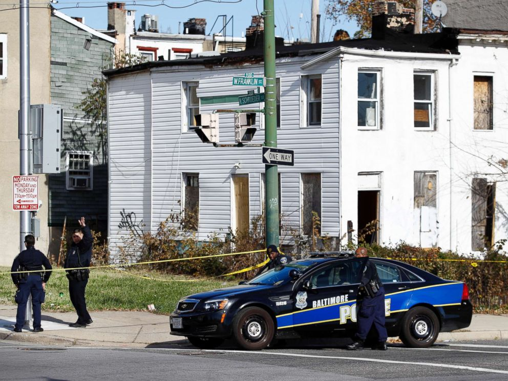 PHOTO: Members of the Baltimore Police Department gather near the scene of the shooting death of Baltimore Police detective Sean Suiter in Baltimore, Nov. 17, 2017.
