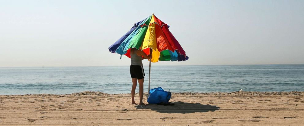 PHOTO: A woman closes her beach umbrella before leaving the beach near Los Angeles, Calif., Oct. 1, 2008.