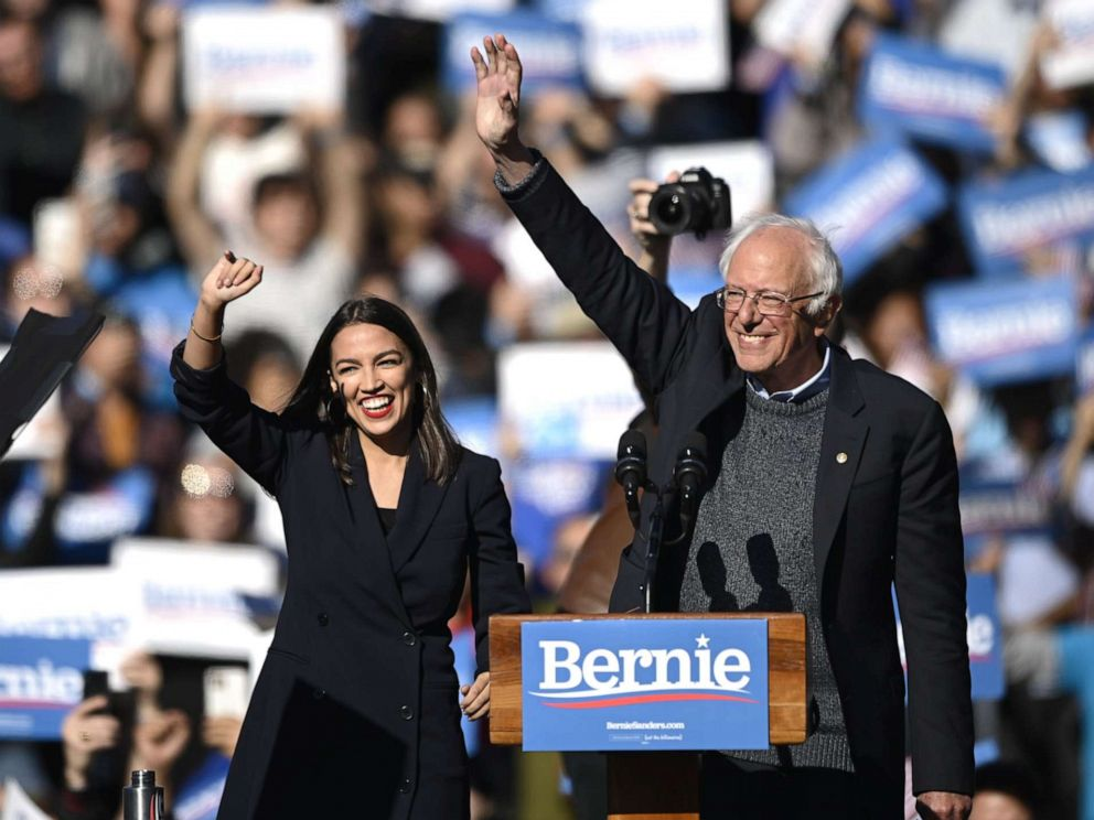 PHOTO: 2020 Democratic presidential hopeful US Senator Bernie Sanders (D-VT) and representative Alexandria Ocasio-Cortez (D-NY) wave to a crowd of supporters during a campaign rally on October 19, 2019 in New York City.