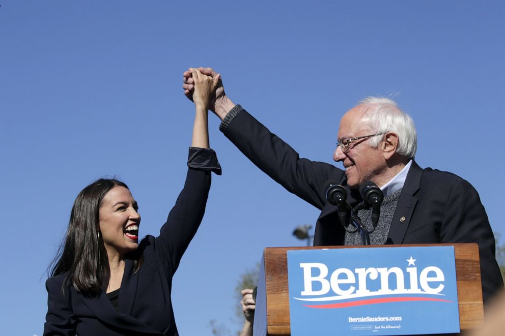 PHOTO: Democratic presidential candidate, Sen. Bernie Sanders (D-VT) holds hands with Rep. Alexandria Ocasio-Cortez (D-NY) during his speech at a campaign rally in Queensbridge Park on October 19, 2019 in the Queens borough of New York City.