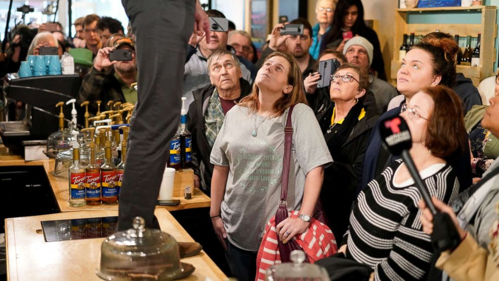 Attendees listen as Democratic 2020 presidential candidate Beto O'Rourke, standing on counter, speaks during a campaign stop at a coffee house in Burlington, Iowa, March 14, 2019.