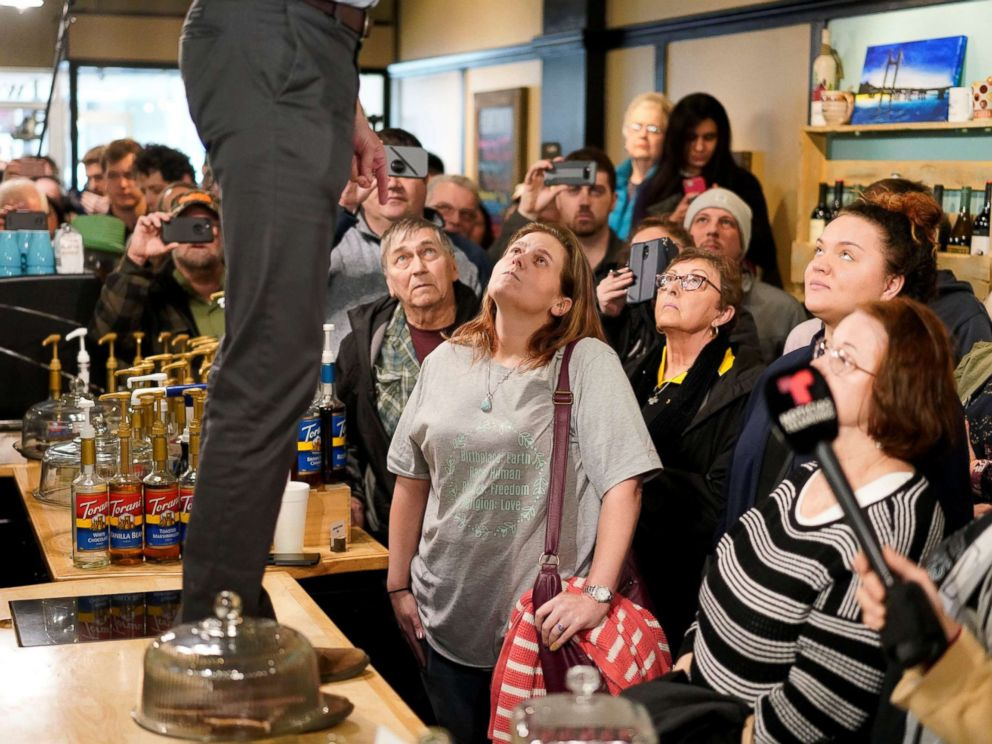 PHOTO: Attendees listen as Democratic 2020 presidential candidate Beto ORourke, standing on counter, speaks during a campaign stop at a coffee house in Burlington, Iowa, March 14, 2019.