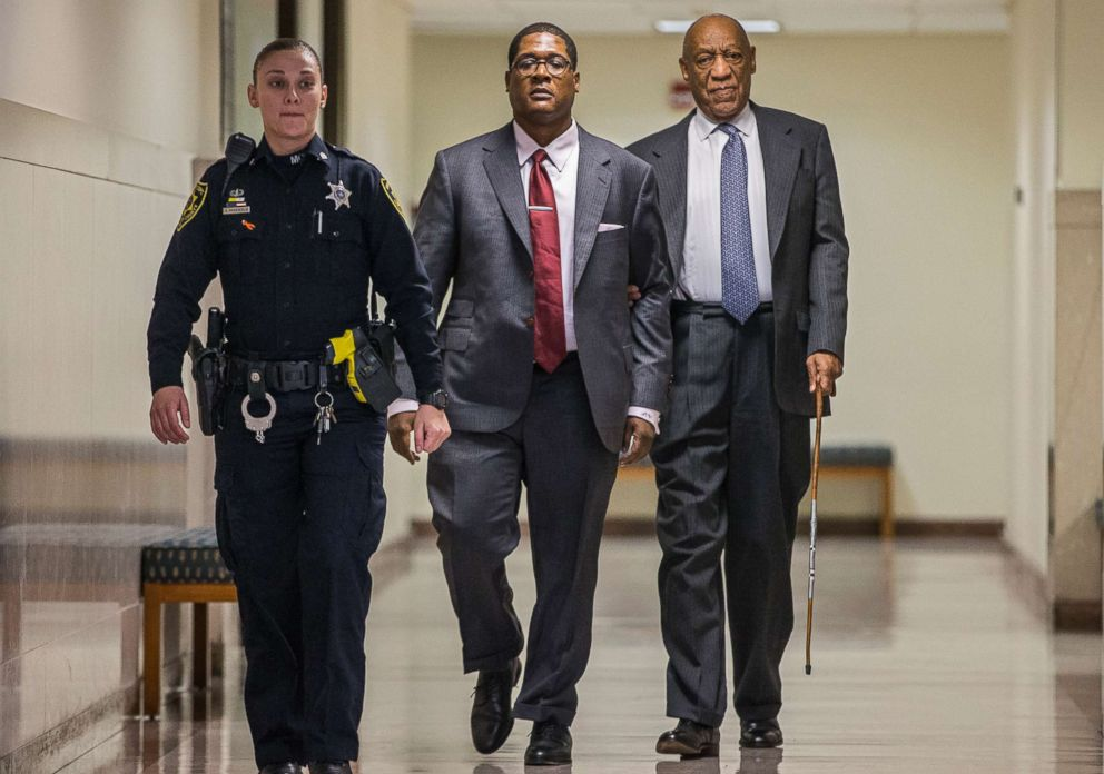 PHOTO: Bill Cosby, right, holds onto Andrew Wyatt as they are escorted by an officer for a short break during the second day of jury selection in his sexual assault retrial, at the Montgomery County Courthouse in Norristown, Pa., April 3, 2018.