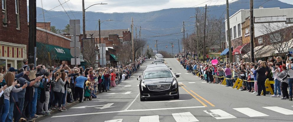 PHOTO: People line the street to pay respects as the hearse carrying the body of Rev. Billy Graham travels through Black Mountain, N.C., Feb. 24, 2018.