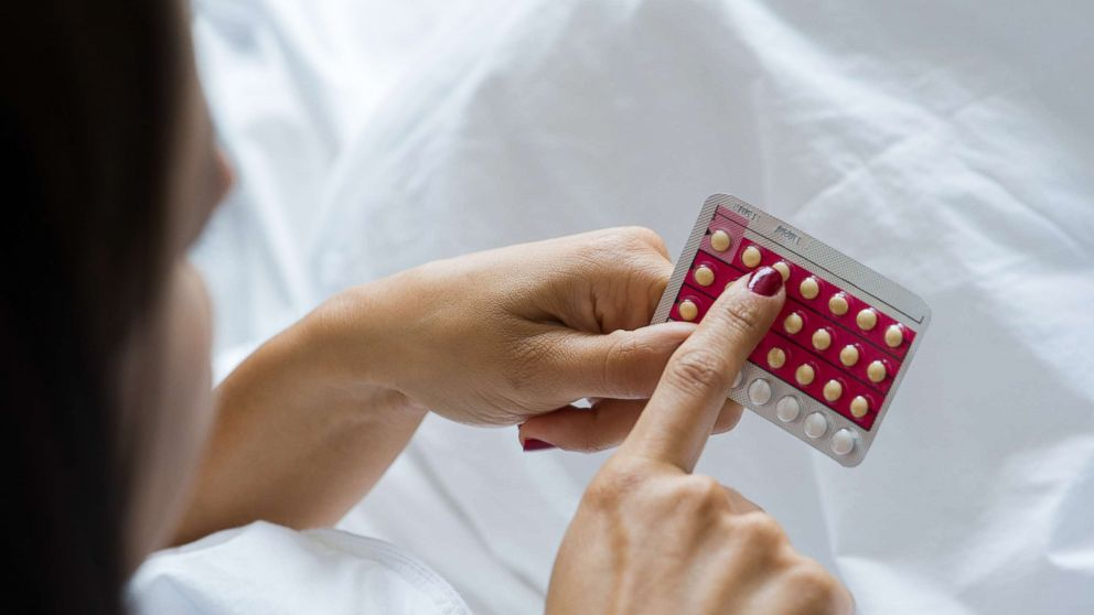 Stock image of woman holding birth control pills.