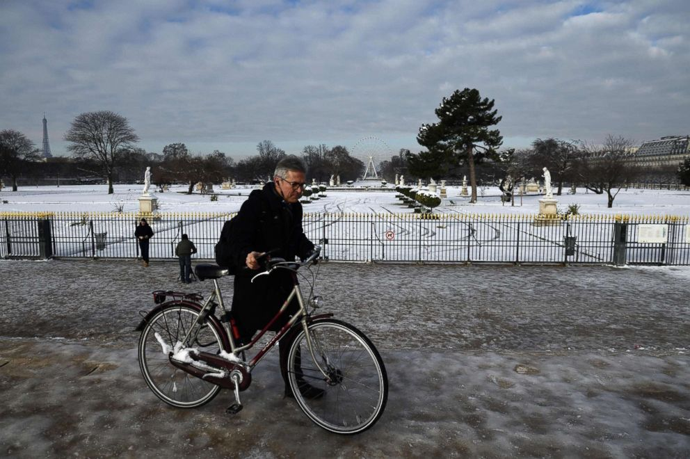 PHOTO: A man pushes his bicycle on black ice past the snow-covered Tuileries Gardens, which remains closed following snowfall, Feb. 8, 2018 in Paris.