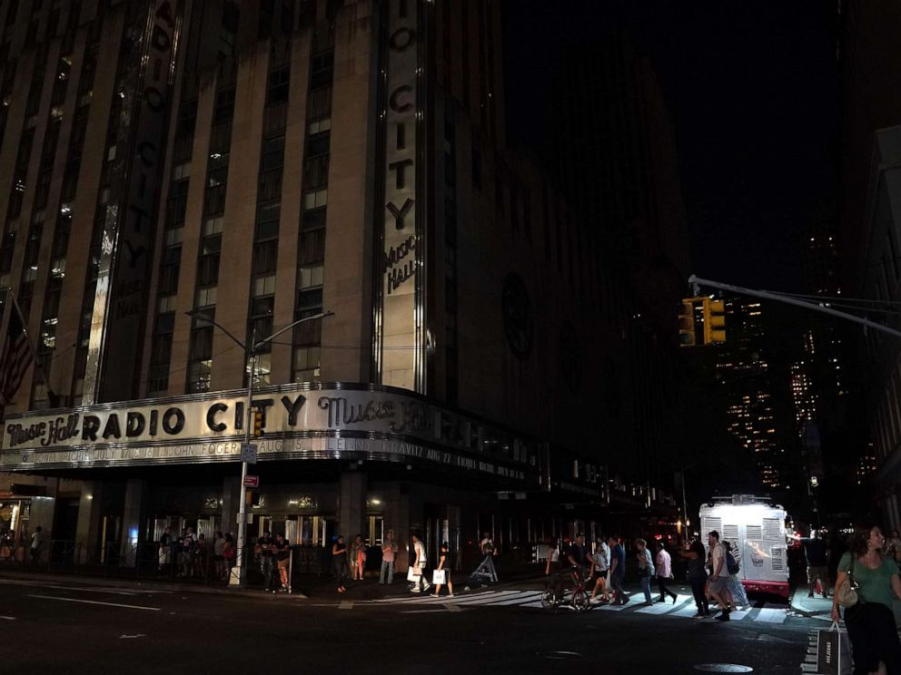 PHOTO: People walk past Radio City Music Hall in the dark during a major power outage affecting parts of New York, July 13, 2019.