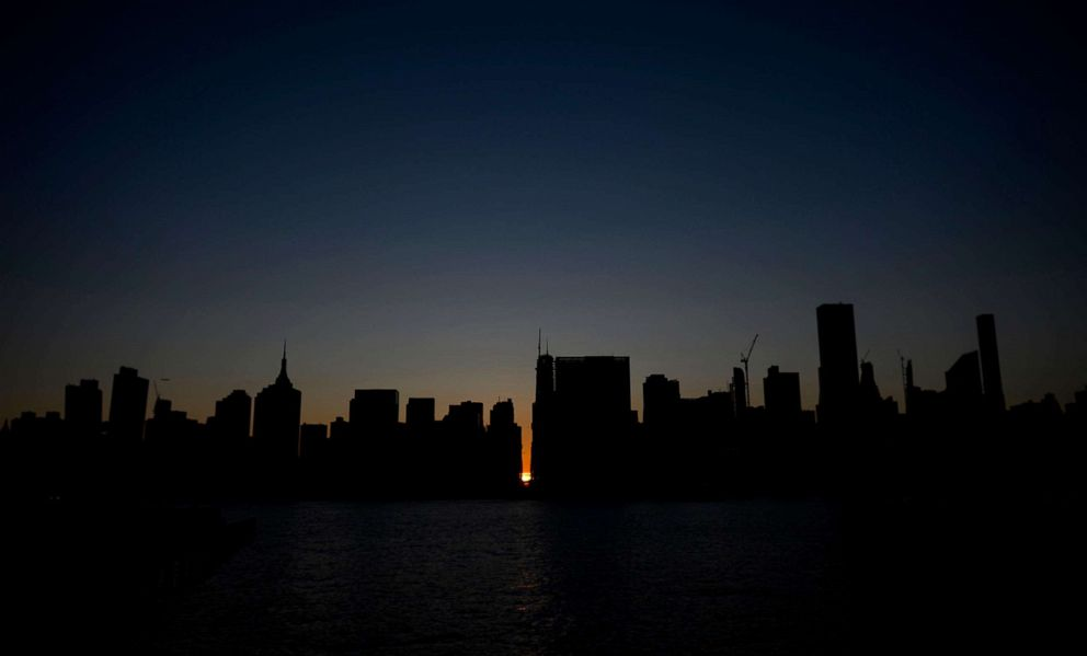 PHOTO: The sun sets behind 42nd Street in Manhattan during a power outage in New York, July 13, 2019.