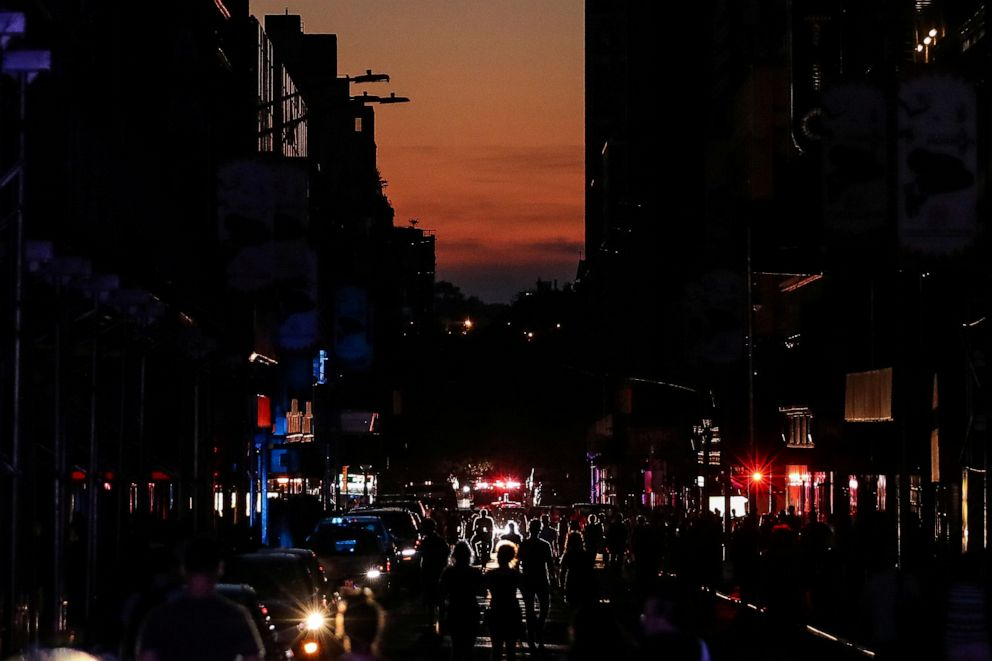 PHOTO: People walk along a dark street near Times Square during a blackout in New York, July 13, 2019.
