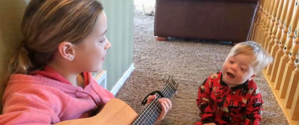 """PHOTO: Lydia Gray, 11, sings """"You Are My Sunshine"""" to her brother Bo Gray, 25 months. Their mother, Amanda Bowman Gray, said Bo Gray, who has Down syndrome, and his vocabulary had blossomed thanked to music therapy and these little jam sessions."""