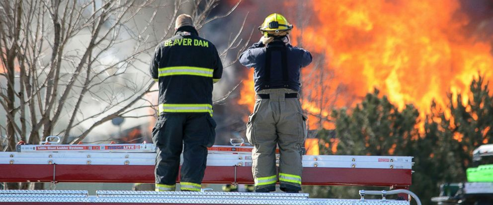 PHOTO: Two firefighters stand atop a truck while watching view the flames of the 109 building of Village Glen Apartments in Beaver Dam, Wisc., March 15, 2018.