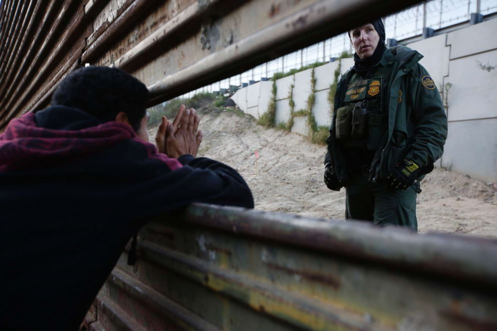 A Honduran migrant, left, talks with a Border Patrol agent as he tries to cross over the U.S. border wall to San Diego, California, from Playas in in Tijuana, Mexico, Dec. 15, 2018.
