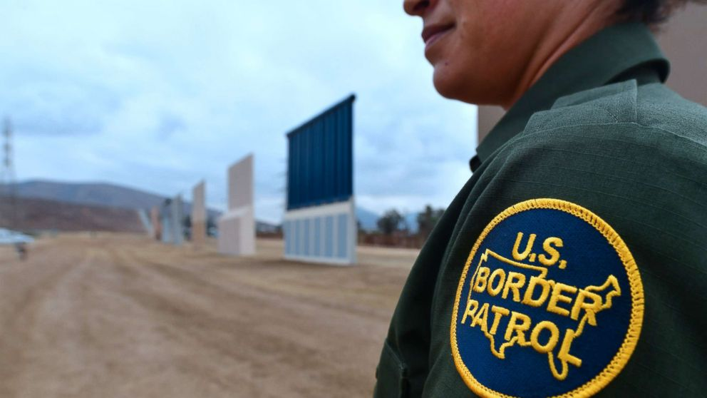 A U.S. Border Patrol officer stands near prototypes of US President Donald Trump's proposed border wall, Nov. 1, 2017, in San Diego, Calif.