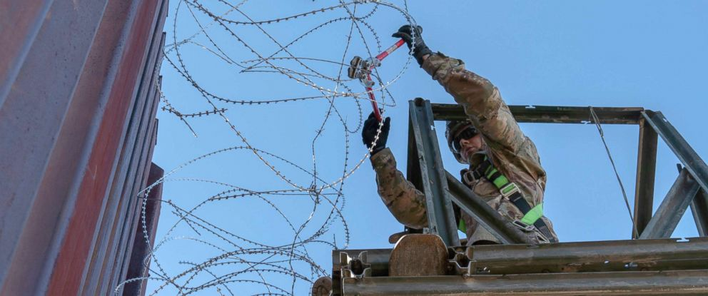 PHOTO: A Soldier with the 515th Sapper Company, 5th Engineer Battalion, 36th Engineer Brigade, cuts off loose strands of concertina wire along the border infrastructure near the DeConcini Port of Entry, Dec. 19, 2018, in Nogales, Arizona.