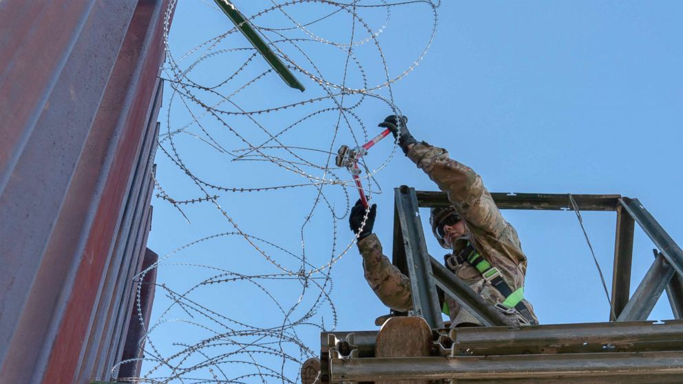 A Soldier with the 515th Sapper Company, 5th Engineer Battalion, 36th Engineer Brigade, cuts off loose strands of concertina wire along the border infrastructure near the DeConcini Port of Entry, Dec. 19, 2018, in Nogales, Arizona.