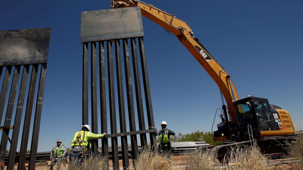 Construction workers place a panel of new bollard wall with the help of heavy machinery in Santa Teresa, New Mexico, as seen from the Mexican side of the border in San Jeronimo, on the outskirts of Ciudad Juarez, Mexico, April 23, 2018.