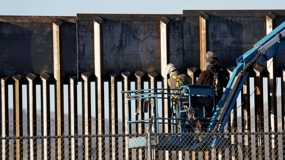 People work on the U.S./Mexican border wall, Feb. 12, 2019, in El Paso, Texas.