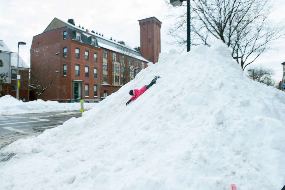 PHOTO: A child slides down a 20 foot pile of snow after the Blizzard of 2015 in the South End of Boston, Mass. on Jan. 27, 2015,