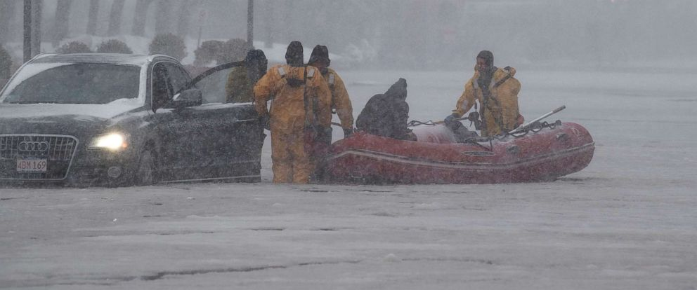 PHOTO: Firefighters wearing ice rescue suits help a stranded motorist, in Boston, Mass., Jan. 4, 2018.