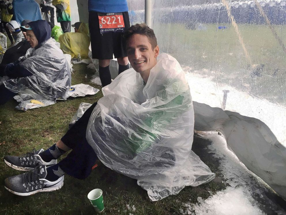PHOTO: Connor Buchholz, 25, of Toledo, Ohio, waits under a tent beside ice crystals that accumulated at the athletes village before the start of the the 122nd Boston Marathon, April 16, 2018, in Hopkinton, Mass.