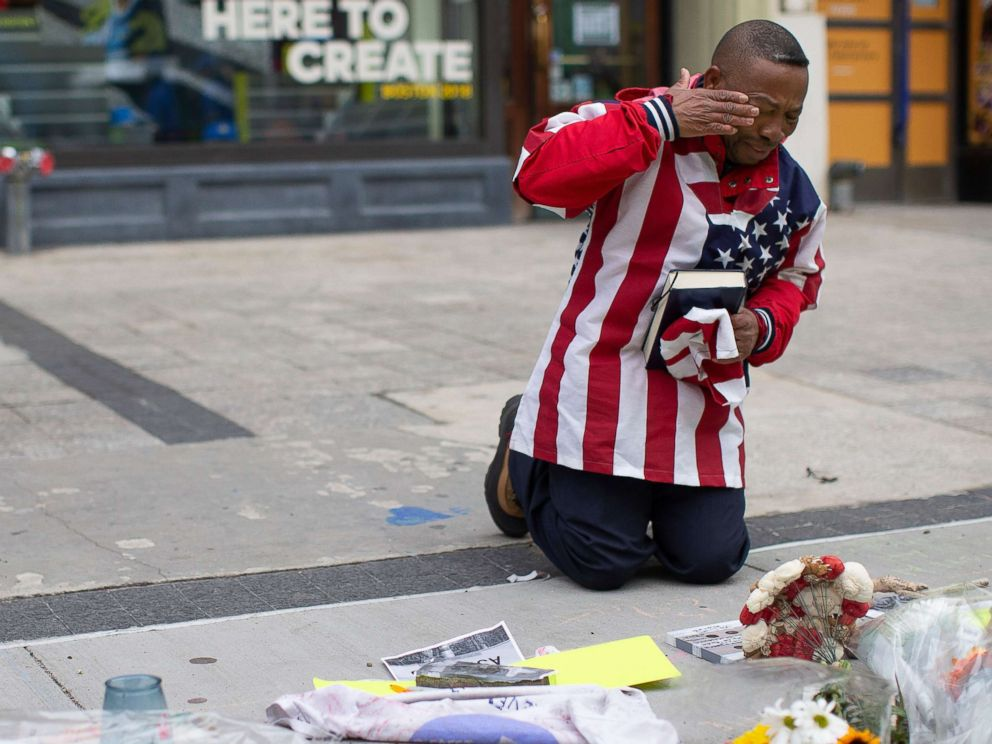 Christopher Nzenwa wipes tears away after praying at a memorial outside of Marathon Sports at the location of the first explosion, during a memorial ceremony on the fifth anniversary of the Boston Marathon Bombing in Boston, April 15, 2018.