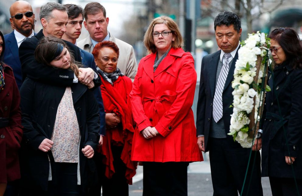 The family of Lu, Jun Lu observe a moment of silence with the family of Martin Richard, foreground during a ceremony at the site where Martin Richard and Lingzi Lu were killed in the second explosion at the 2013 Boston Marathon, April 15, 2018, in Boston.