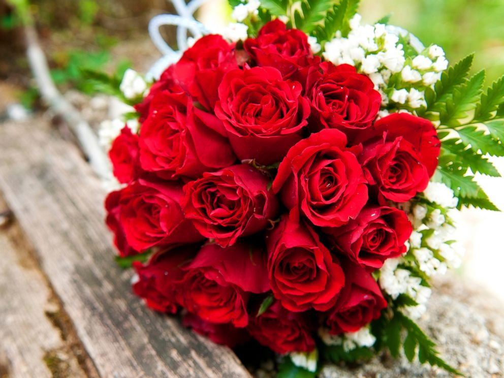 PHOTO: A bouquet of red roses lays on a wooden picnic bench in this stock image.