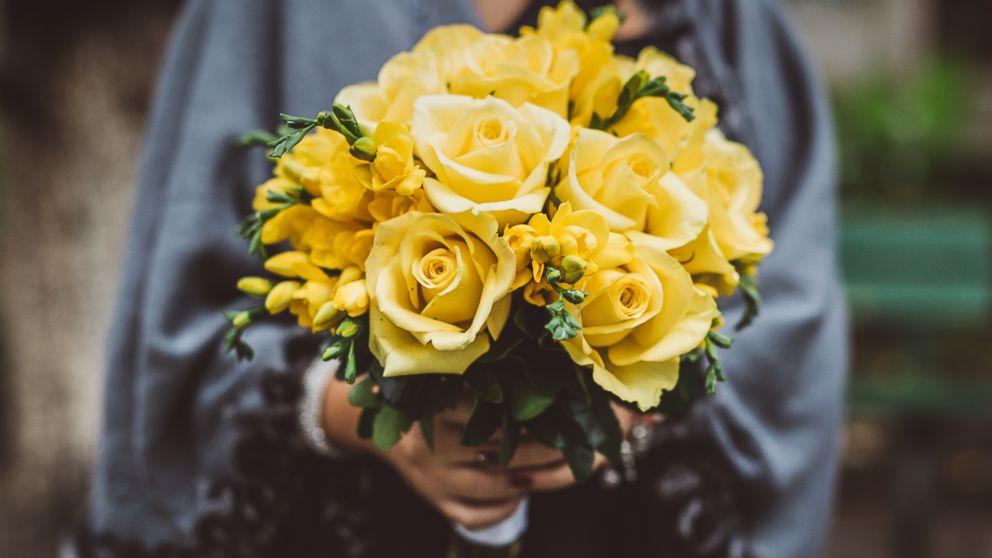 A woman holds a bouquet of yellow roses in this stock image.